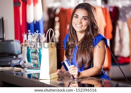 Pretty Hispanic woman buying some clothes with a credit card - stock photo