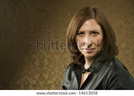 Pretty Hispanic Woman in front of Gold Wallpaper - stock photo