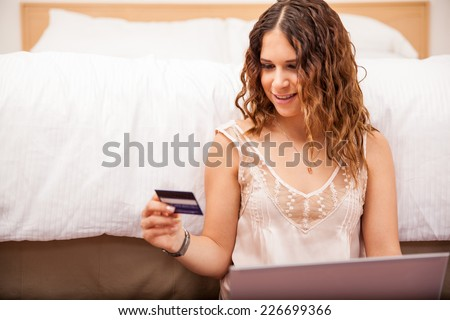 Pretty Hispanic woman using her credit card to buy some clothes online