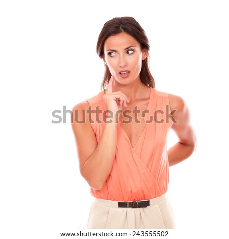 Pretty hispanic woman with hand on chin wondering while looking to her right in white background - copyspace - stock photo