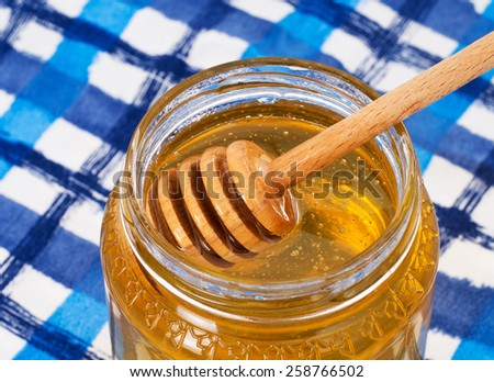 Pretty honey pot on blue and white tablecloth. With wooden dipper. Closeup. - stock photo