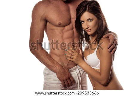 Pretty Hot Woman Seductively Looking at Camera White Touching Partners Perfect Abs, Isolated on White. - stock photo