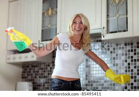 Pretty housewife finished cleaning the kitchen - stock photo