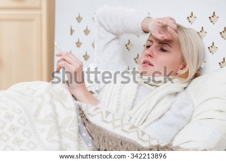 Pretty ill woman has a cold and fever. She is lying in bed and touching her forehead. The girl is holding thermometer and looking at it with desperation