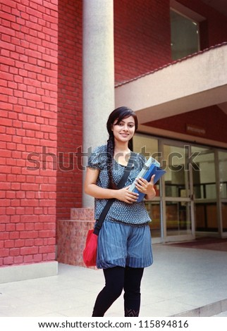 Pretty Indian / Asian college student standing outside the campus building with books in hand. - stock photo
