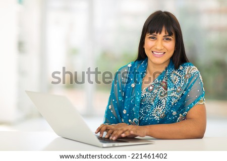 pretty indian businesswoman using laptop in office - stock photo