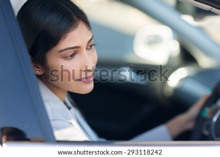 pretty indian woman driving her new car - stock photo
