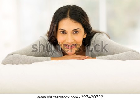 pretty indian woman lying on bed at home - stock photo