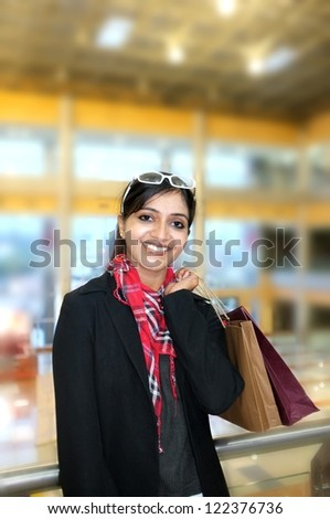 Pretty Indian woman smiling with lots of shopping bags. - stock photo