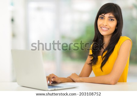 pretty indian woman using laptop at home - stock photo