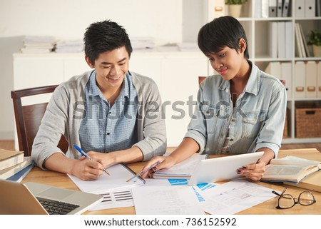 Pretty Indonesian girl helping her fellow student with homework
