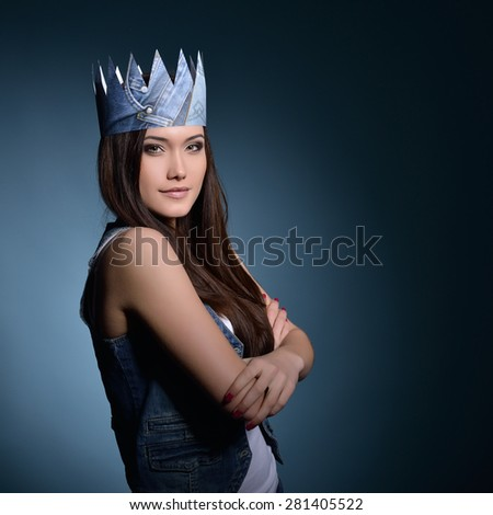 Pretty jeans princess. Beautiful girl in jeans and paper crown over blue background. - stock photo