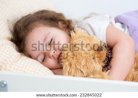Pretty kid  little girl sleeping in a bed - stock photo