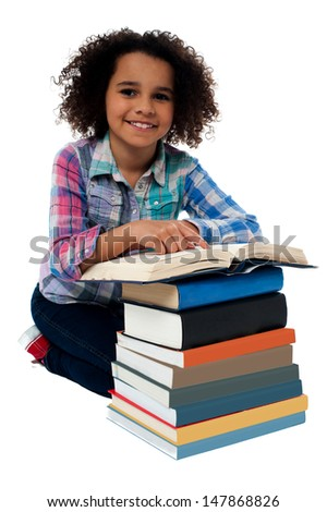 Pretty kid reading textbook from the pile of books - stock photo