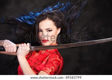 Pretty kimono woman in action with katana/sword - stock photo