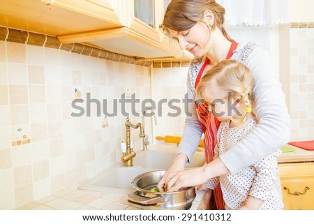 Pretty ladies in the kitchen cooking together. - stock photo