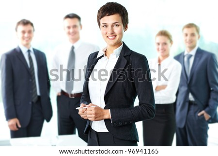 Pretty lady being a successful businesswoman at the head of a strong team