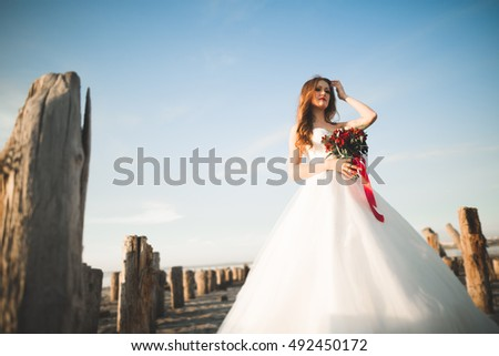 Pretty lady, bride posing in a wedding dress near sea on sunset