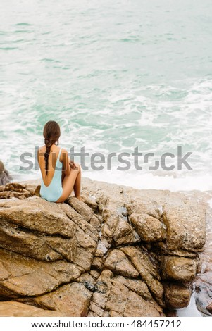 Pretty lady in full body swimsuit with long healthy hairs sit on big stone on the rock beach during sea ocean storm. Big waves near her legs. View from back. Concept of danger, sad, bad emotions.