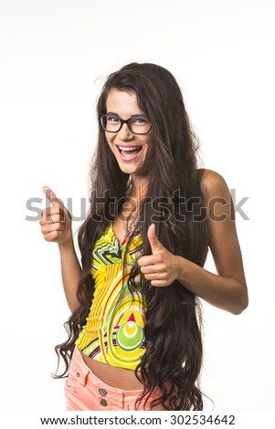 Pretty lady in glasses is smiling on the white background. Charming girl is showing big fingers up. - stock photo