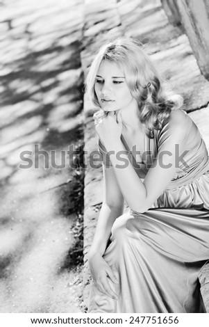 pretty lady sitting in sun light near the columns - stock photo