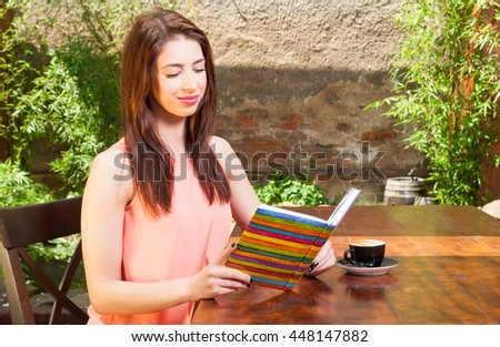 Pretty lady sitting on terrace and reading from notebook or agenda with coffee aside and copy space area
