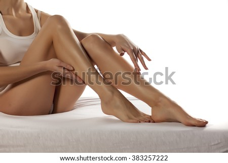 pretty lady touching her bare legs - stock photo