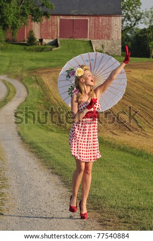 pretty lady walking in the country side with umbrella - stock photo