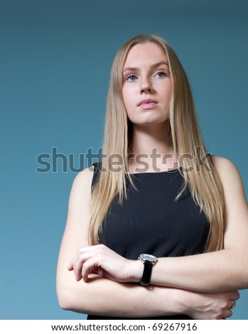 Pretty lady wearing fashionable dress. Fresh new young face. Studio waist shot, uniform background. Hands folded on the chest. - stock photo