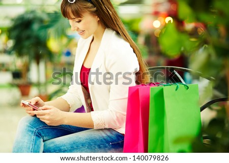 Pretty lady with colorful shopping bags sitting in trade center and writing sms