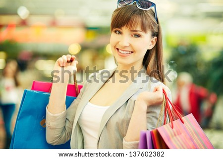 Pretty lady with colorful shopping bags smiling at camera