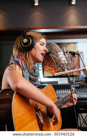 Pretty Latin woman singing and playing guitar in recording studio - stock photo