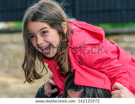 pretty laughing child perched on the shoulder of her mother - stock photo