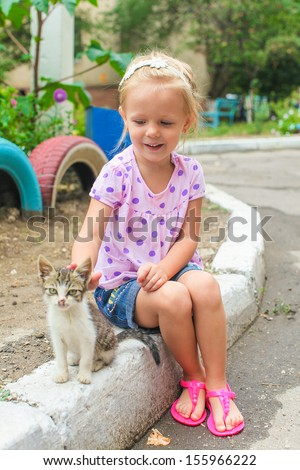 Pretty Little beautiful girl plays with a homeless small kitten - stock photo