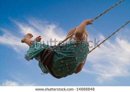 Pretty little blond girl on a swing against a beautiful blue sky background.