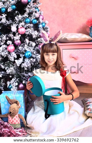 pretty little blond girl under decorated christmas tree with presents