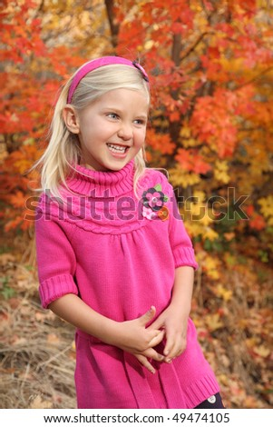 pretty little blond girl with big smile outside with fall colors - stock photo