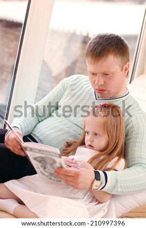 Pretty little blonde girl and father sit near window and read book - stock photo