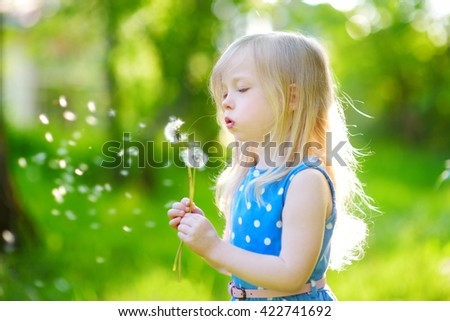 Pretty little blonde girl blowing off a dandelion on beautiful sunny summer day - stock photo