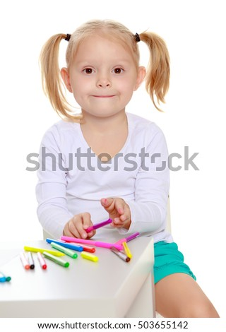 Pretty little blonde girl drawing with markers at the table.Girl holding in hands a pink marker.Isolated on white background