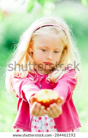 Pretty little blonde girl holding a bitten apple, an looking sad - stock photo