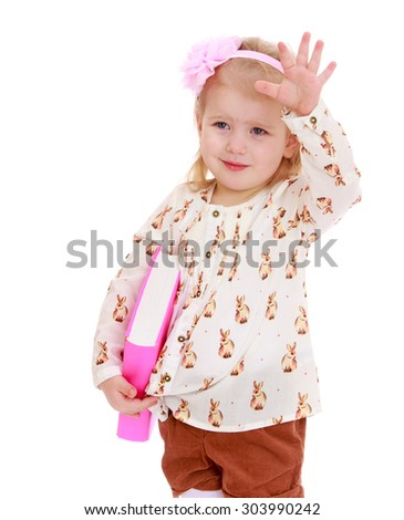 Pretty little blonde girl in brown shorts and a white t-shirt holding a thick book. On the head the girl has a beautiful pink bow.Girl waving with his free hand , close-up-Isolated on white background - stock photo