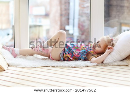 Pretty little blonde girl laughs and lies on white pillow and fur near window in room - stock photo