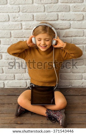 Pretty little blonde girl listening to music on tablet and smiling while sitting cross-legged against white brick wall - stock photo