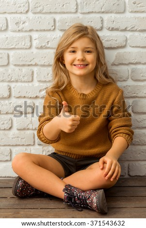 Pretty little blonde girl looking in camera, smiling and showing OK sign while sitting cross-legged against white brick wall - stock photo