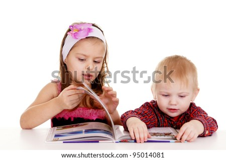 pretty little  boy and girl reading at table - stock photo