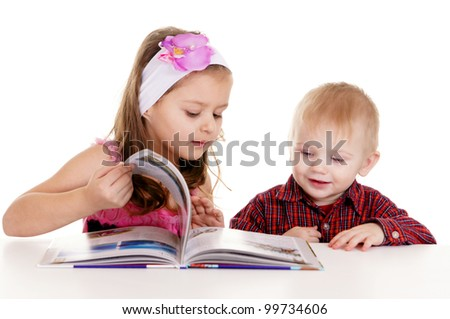 pretty little  boy and girl reading at table