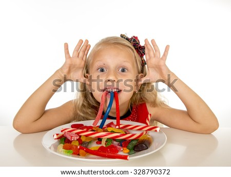 pretty little female child eating dish full of candy caramel and sweet food in sugar abuse and unhealthy diet, bad habit nutrition concept isolated on white background - stock photo