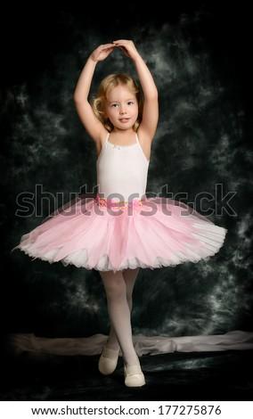 Pretty little girl ballerina in tutu posing over vintage background. - stock photo