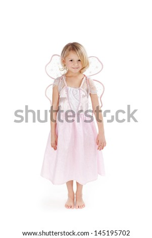 Pretty little girl dressed as a pink fairy with wings standing in bare feet smiling at the camera, on white